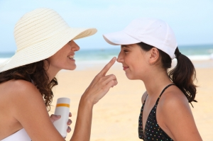 Mother spreading sunscreen on her daughter's face